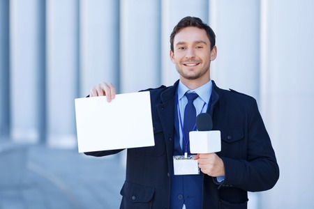 correspondent: Time for tidings. Attractive correspondent with microphone wears a smile while holding a sheet of paper.