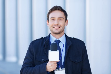 newscast: Ready to take down. Young journalist looks confident before taking down another newscast. Stock Photo