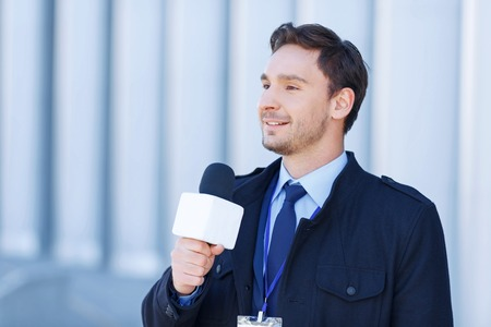 newsman: Process of recording. Young confident reporter is in a process of taking down news report. Stock Photo