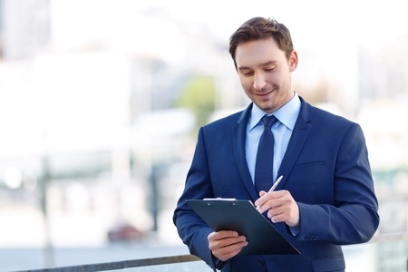 appealing: Checking the list. Appealing young gentleman on the balcony smiles satisfied while using a clipboard. Stock Photo