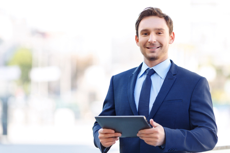 Perfect results. Nice-looking young businessman is smiling brightly while holding a portable electronic tablet.