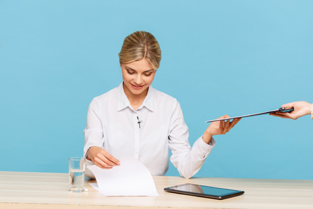 upbeat: Take it. Agreeable attractive upbeat TV announcer holding folder and looking through papers while preparing for work