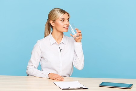 grey water: Take a break. Upbeat positive professional TV announcer holding glass and drinking water while sitting at the table Stock Photo