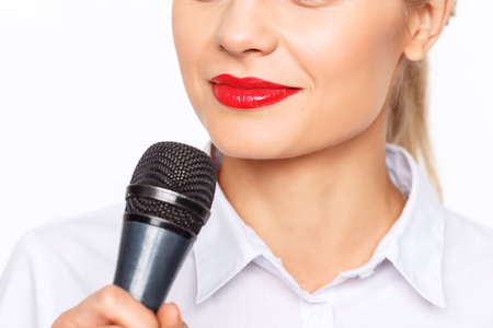 feeling up: Ready to do my job. Close up of pleasant young attractive television host holding microphone and interviewing while feeling delighted Stock Photo