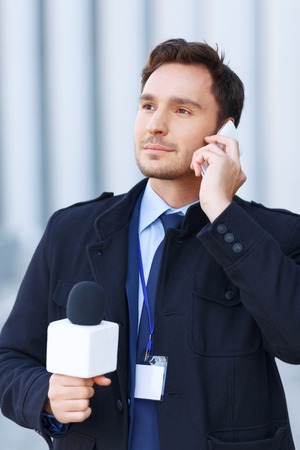 newsman: Listening considerately. Eye-catching newsman looks focused while listening to narrator over the smartphone.