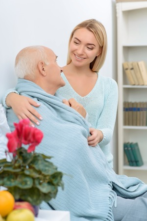 feeble: Love my granddad. Smiling granddaughter looks kind and sincerely happy while wrapping her granddad in blanket. Stock Photo