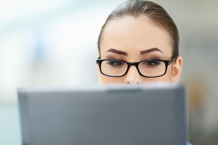 entities: Checking data. Young female employee looks into the monitor and is being reasonably focused. Stock Photo