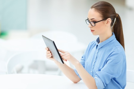 entities: Essential issues. Young female employee is busy completing office task on digital tablet Stock Photo