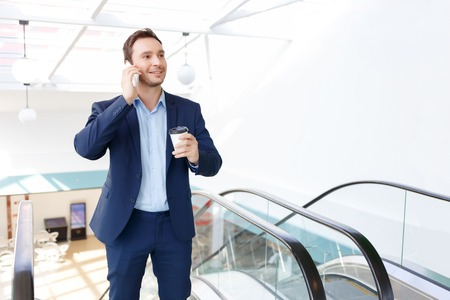 personal call: Time to chill. Office worker is using his personal break time to call his acquaintance and drink some coffee Stock Photo