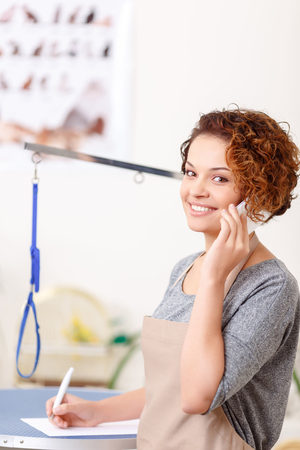 groomer: Another client.  Attractive young female groomer is making an appointment at the salon. Stock Photo