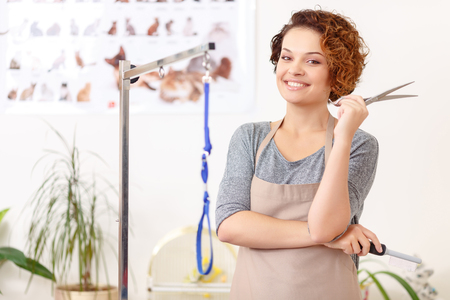 vividly: Ready to start. Attractive female groomer is smiling vividly while holding her hairdo necessaries. Stock Photo