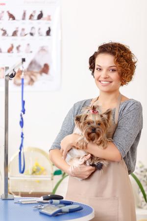 mujer con perro: Mi cliente Yorkshire. Buen aspecto groomer femenina está sonriendo alegremente mientras sostiene en sus brazos encantadora terrier Yorkshire.