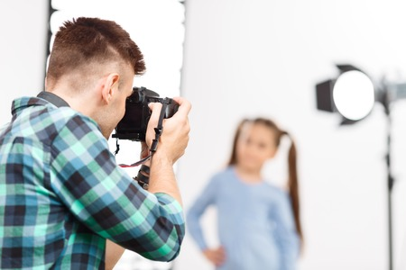 Photographer in motion. Young handsome photographer upholds his camera while shooting. Stock Photo