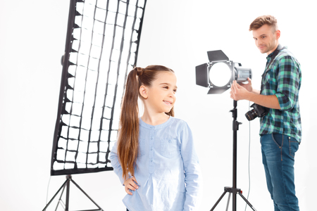 sincere girl: Lighting correction. Handsome male photographer fixes spotlight beside the posing small model. Stock Photo