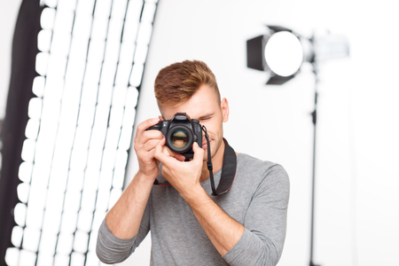 equipping: Photographer pose. Young handsome professional photographer stands in the pose of making pictures while holding his camera.