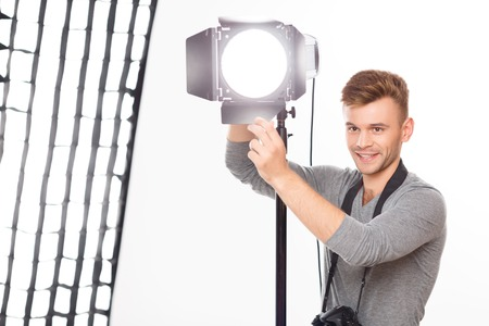 Lighting course correction. Young male attractive photographer is smiling while changing light force and direction.