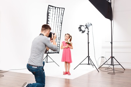 handsome: Photoshoot in progress. Young handsome male photographer in the process of taking photos of small model girl. Stock Photo