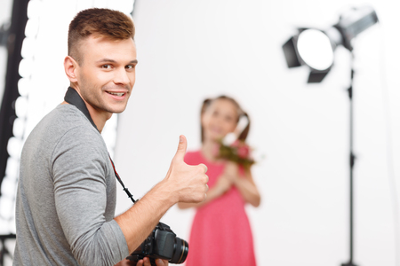 workroom: Creation time. Nice-looking male photographer shows thumbs up and smiles before making photos of his little model. Stock Photo