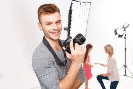 charmingly: Loving my job. Appealing young male photographer with his camera grins charmingly while model and makeup artist are both busy preparing. Stock Photo