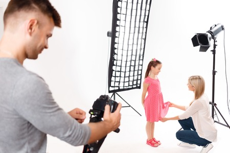 'getting ready': Arrangement finishing. Young male photographer fiddles with camera while little girl is getting ready to shooting
