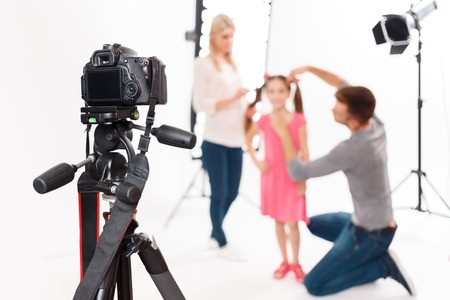 workroom: Camera is supported. Photographer leaves his camera fixed safely while helping to prepare little girl for shooting Stock Photo