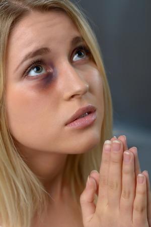desperate: Sin esperanza. Desesperado pobre mujer golpeada tomados de la mano juntos mientras rezaba Foto de archivo