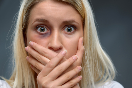 heed: What a terror. Close up of frustrated young beaten girl holding her hands on the mouth and expressing fear while standing isolated on grey background