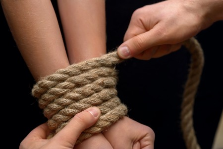bonding rope: Do not do it. Close up of man bonding he hands of poor young girl with rope
