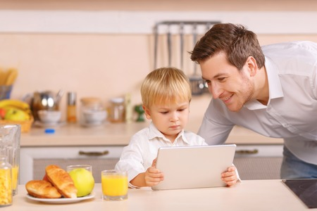 descubridor: descubridor Petite. El niño se siente seguro con el uso de dispositivos tales como el bloc de notas digital. Foto de archivo