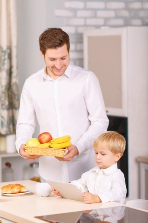 basketful: Occupied little guy. Dad watches his son using his digital notepad while holding a basketful of fruits.