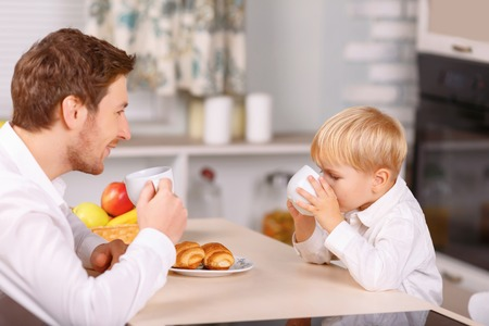 refreshments: Similar gestures. Dad and his little son look very similar when drinking refreshments from porcelain cups. Stock Photo