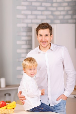 sincerely: Picture perfect. Father and his little son are both posing in the kitchen and smiling sincerely.