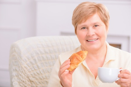 agreeable: Home is best. Portrait of agreeable content adult woman holding croissant and drinking tea while resting at home Stock Photo