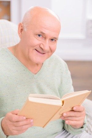 man holding book: Like books. Close up of adult content pleasant man holding book and reveling in reading while feeling content Stock Photo