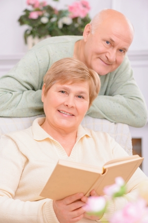 to be pleasant: Content to be together. Pleasant adult positive woman sitting in the armchair and reading book with her husband standing nearby Stock Photo