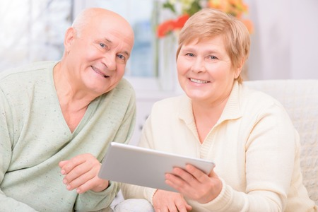 agreeable: Keep pace of time. Agreeable loving happy couple sitting on the sofa and holding laptop  while expressing joy