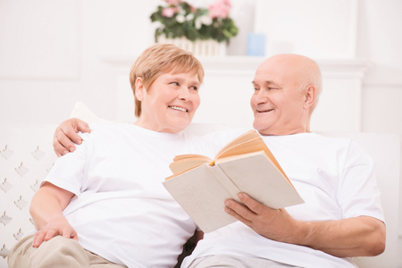 to be pleasant: Happy to be together. Pleasant delighted adult couple lying on bed and reading book while bonding to each other