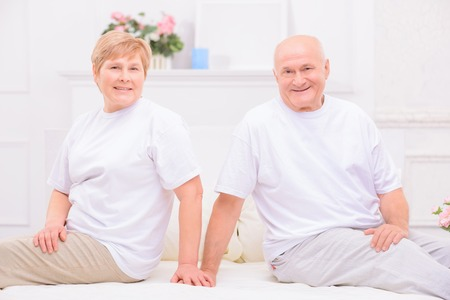 agreeable: Happy family life. Agreeable pleasant adult couple sitting on bed and expressing positivity while resting at home Stock Photo