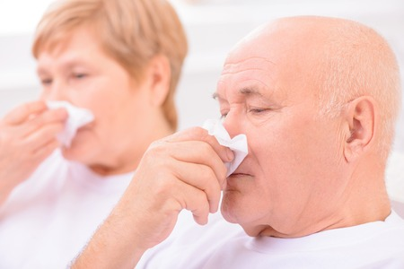 running nose: Improve your health. Close up of unhealthy loving couple having running nose and feeling ill while blowing their noses Stock Photo