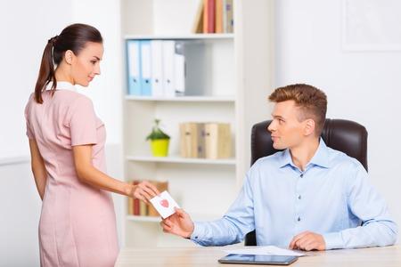 mujer trabajadora: nota secreta. Mujer atractiva joven se detiene en la mesa para pasar una carta de amor a su pareja rom�ntica.