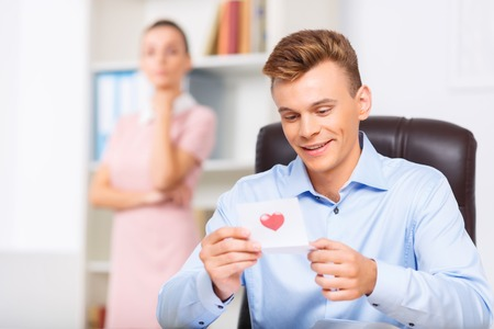 tenderly: Love buzz. Handsome male office worker smiles tenderly while reading the note from his beloved woman. Stock Photo