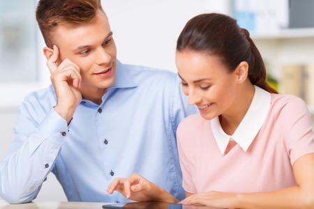 working ethic: Loving look.  Handsome young office manager watches his beloved female coworker while she is working with digital notepad.