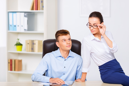 woman pose: Workroom romance. Handsome officeman and attractive office woman are posing at the desk.