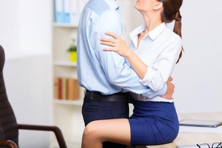 mujer trabajadora: Los juegos previos de Office. Joven pareja encantadora oficina est� ocupado con la celebraci�n de unos a otros en forma apasionada. Foto de archivo