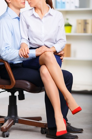 executive woman: Together in office. Pretty assistant is sitting on her partners lap while being embraced tenderly. Stock Photo