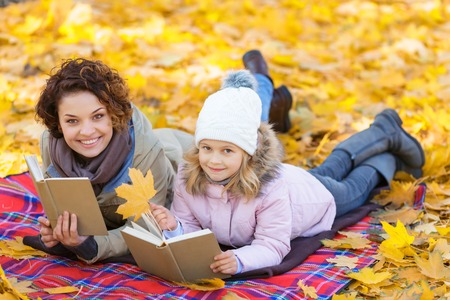 agreeable: Full of positivity. Agreeable happy delighted mother and daughter holding books and reading them while lying on the blanket in park
