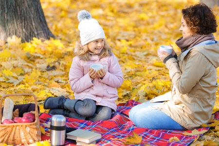 nice: Nice day. Agreeable cheerful daughter and mother drinking tea and having picnic in park while sitting on the blanket