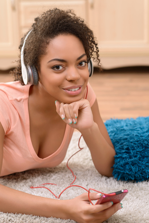 take a break: Take a break. Pleasant cheerful charming girl holding mobile phone and listening to music while expressing joy Stock Photo