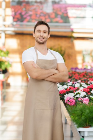 flower seller: Like my work. Pleasant confident handsome flower seller folding his hands and expressing positivity while working in greenhouse