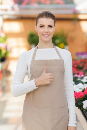up service: Life is great. Positive cheerful florist thumbing up and working while expressing gladness
